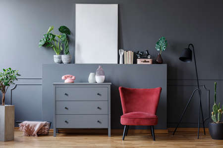 Red chair next to grey cabinet in living room interior with mockup of poster and plants. Real photo Stock Photo