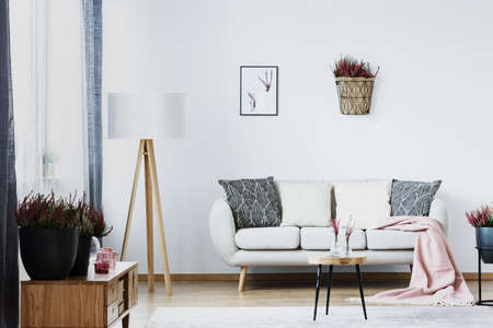 Big lamp standing next to a white couch with cushions in a living room interior Фото со стока - 106381327