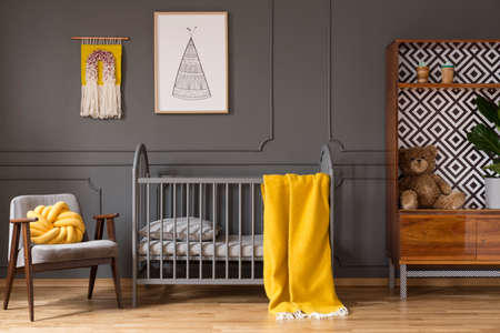 Real photo of a baby room with yellow cot standing between an armchair and a cupboard with teddy bear and a plant in childs interior