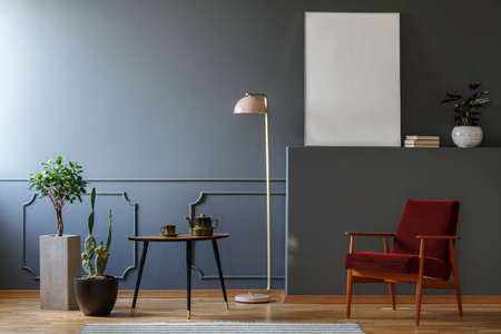 Red wooden armchair in grey living room interior with table between plants and lamp. Real photo