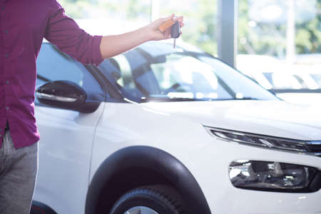 Close-up of buyer with keys in hand to new exclusive car in dealing salon