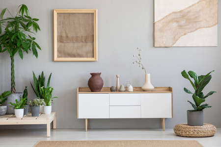 Posters on grey wall above white cupboard in living room interior with plants and pouf. Real photo Foto de archivo
