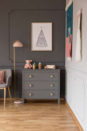 Real photo of a grey cupboard with ornaments standing next to a lamp, armchair and wall with a poster in spacious baby room interior Stockfoto