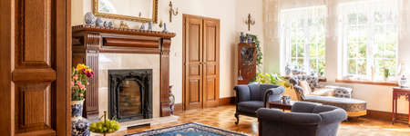 Blue armchairs next to fireplace in elegant living room interior with settee and windows. Real photo Stock Photo