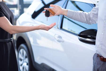 Primer plano de las manos del vendedor con las llaves y el comprador después de la transacción en la sala de exposición de automóviles