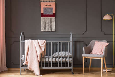 Real photo of a baby crib with a blanket standing next to an armchair with a cushion and a lamp in childs room interior