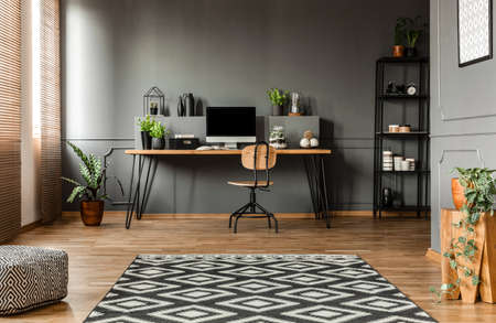 Patterned carpet and pouf in simple grey workspace interior with computer monitor on desk 版權商用圖片