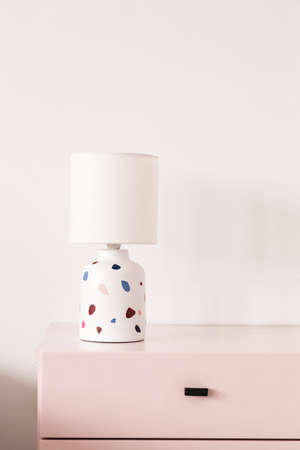 Patterned lamp on pastel pink cabinet against white wall in colorful interior. Real photo