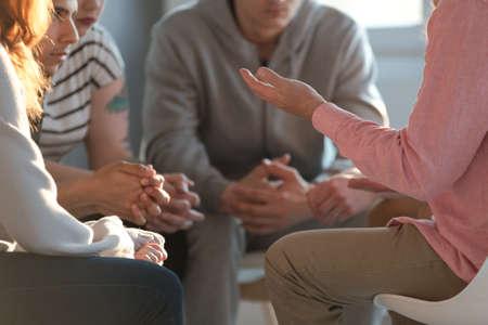 Close-up van een therapeut die gebaart terwijl hij met een groep tieners praat tijdens een educatieve bijeenkomst over zelfacceptatie en motivatie. Stockfoto
