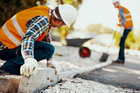 Worker with gloves and in a helmet arranging curbs on the street. Blurred man in the background