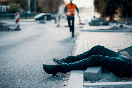 Dead person on the street after an accident at roadworks. Result of non-compliance with health and safety regulations 版權商用圖片