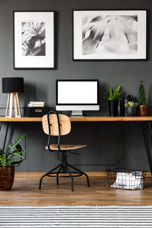 Mockup of empty computer monitor in wooden home office interior with posters on grey wall
