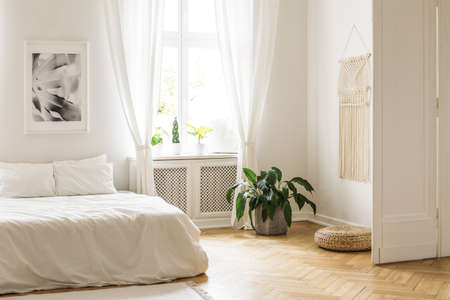 Beige macrame and a poster on the white walls of a bright, minimalist bedroom interior with herringbone hardwood floor and plants Stock Photo