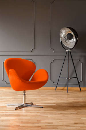 Real photo of orange armchair and big metal studio lamp standing in dark living room interior with wooden floor and molding on the wall Stock Photo