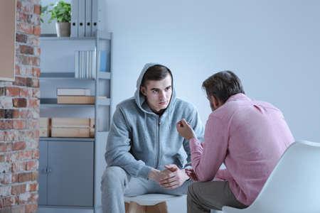 Un especialista en psicología que explica un plan de acción para la recuperación a un adolescente con problemas durante una sesión de terapia individual.