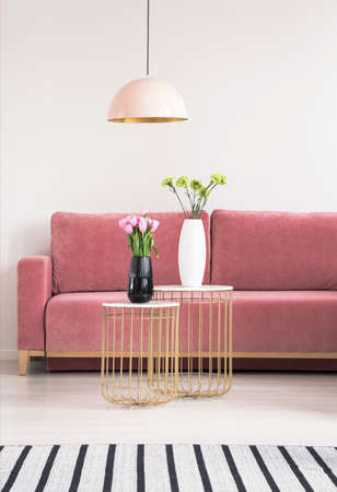 Golden small tables with flowers, pink couch and chandelier in a living room interior. Real photo Stok Fotoğraf - 106516848