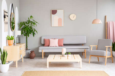 Patterned armchair next to wooden table in flat interior with pink pillows on sofa. Real photo