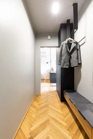 Clothes on rack above countertop in anteroom interior with wooden floor and light. Real photo Stock Photo
