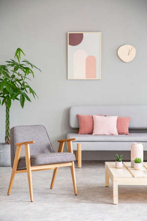 Grey wooden armchair next to table in living room interior with poster above couch. Real photo Stock Photo