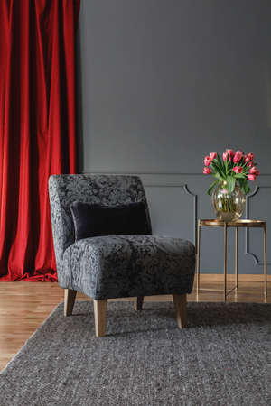 Grey floral chair with black cushion standing on dark carpet in elegant room interior with fresh tulips on gold metal table and red curtain. Empty wall with place for your graphic