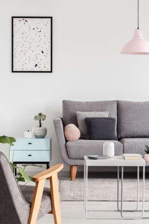 Poster boven kast naast grijze bank in woonkamer interieur met fauteuil en lamp. echte foto