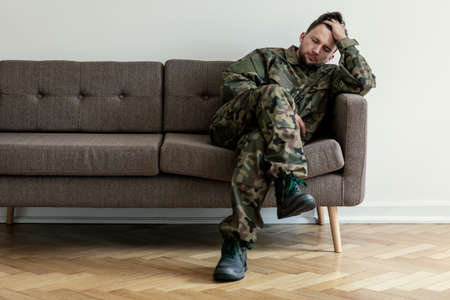 Helpless soldier sitting on a couch while waiting for a therapy session 写真素材