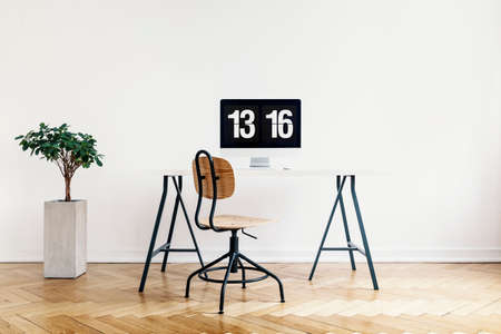 Real photo of a modern home office interior with a computer, desk and chair. Empty wall, place your poster
