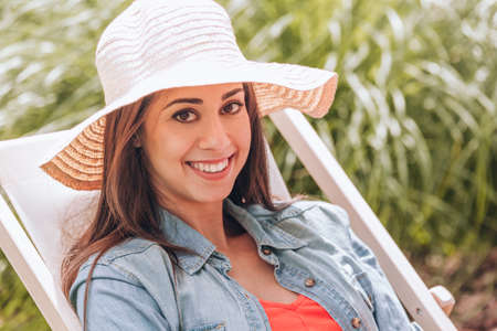 Smiling woman with hat relaxing on sunbed in the summer