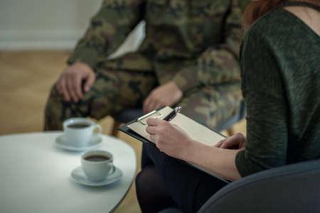Gros plan d'un psychologue écrivant des notes tout en parlant à son patient de l'armée