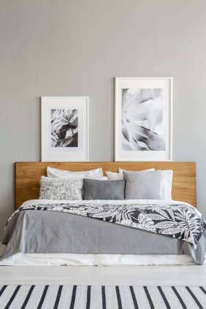 Grey patterned blanket on wooden bed in bedroom interior with posters and carpet. Real photo