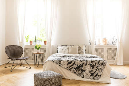 Comfy bedroom interior with a leaf motif bedding on a bed, a rattan chair and a black and white pouf standing on a herringbone parquet. Real photo.