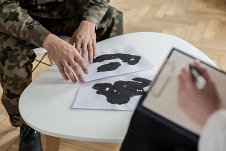 Close-up of soldiers hands touching papers with ink stains during a therapy
