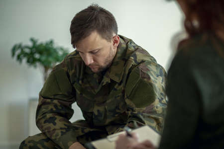 Soldier sitting and talking to his therapist Stock Photo - 106576498
