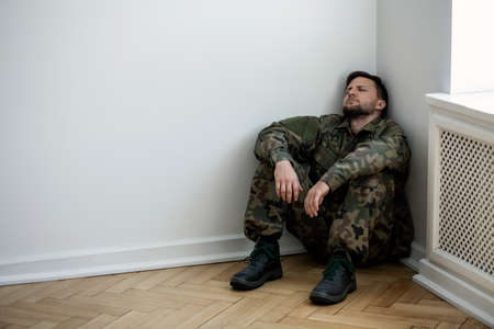 Depressed army man in uniform sitting in a corner of an empty room. Place for your poster on the wall