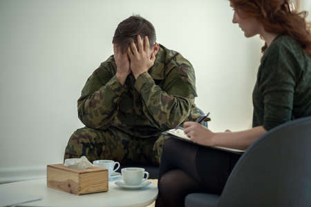 Soldier hiding his face in his hands while talking to a psychiatrist during therapy