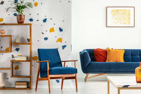 Armchair and couch with pillows in blue and orange living room interior with poster and plant. Real photo