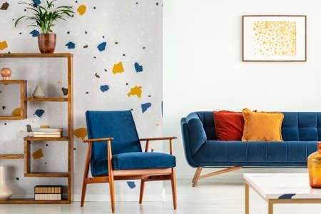 Sillón y sofá con almohadas en el interior de la sala de estar azul y naranja con cartel y planta. Foto real