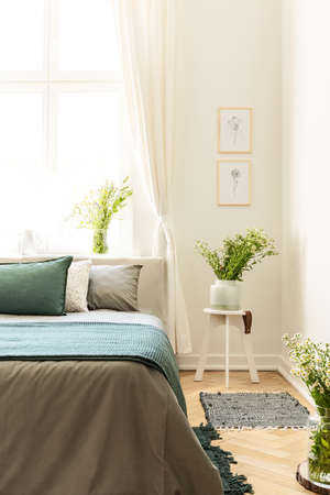 Posters on white wall above flowers on table next to grey and green bed in bedroom interior. Real photo