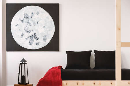 Red blanket and black pillows on wooden bed in bedroom interior with moon poster and lantern. Real photo Stock Photo