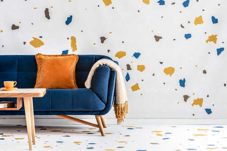 Orange pillow and blanket on navy blue sofa in colorful living room interior with table. Real photo