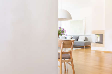 White empty wall with copy space in living room interior with chair and wooden floor. Real photo with a place for your light switch