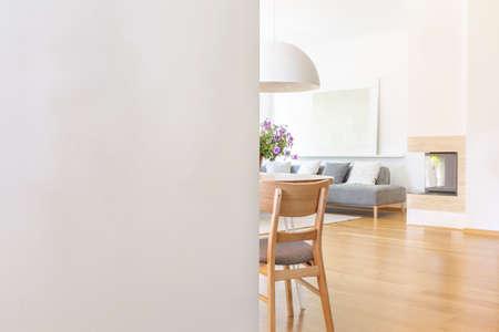 Parete vuota bianca con lo spazio della copia nell'interiore del salone con sedia e pavimento in legno. Foto reale con un posto per l'interruttore della luce