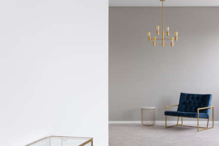 Gold chandelier above blue armchair in elegant living room interior in blurred background. Real photo with focus on an empty place on the wall for your product 写真素材