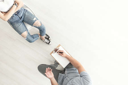 Top view on counselor talking to a difficult teenager. Copy space on background