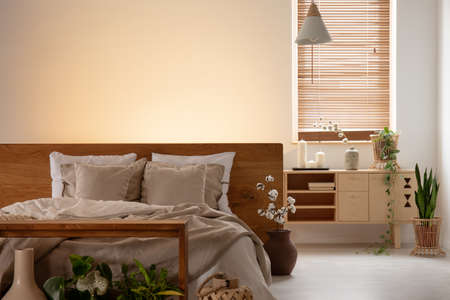 Empty wall in a bedroom interior with a double bed, pillows, cabinet and window blinds. Real photo