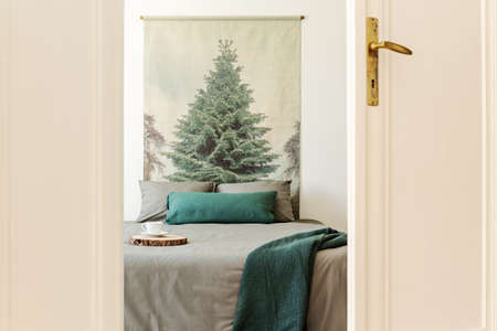 Green blanket on grey bed against tree painting in white simple bedroom interior. Real photo