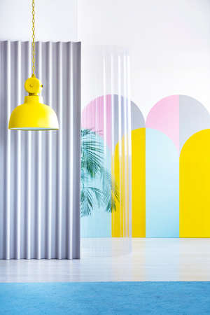 Real photo of a bright yellow, industrial lamp hanging in a geometric interior with pastel arches as wall decoration and plastic screens