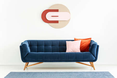 Pink and orange pillows on blue sofa in white apartment interior with poster and carpet. Real photo Stok Fotoğraf - 106560106