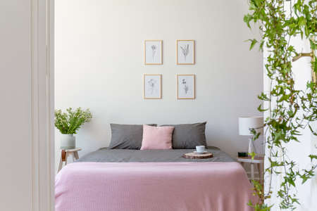 Grey pillows on pink bed in bright hotel bedroom interior with posters and flowers. Real photo
