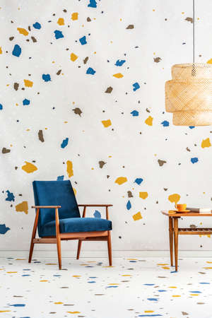 Navy blue armchair next to wooden table in modern flat interior with lamp and wallpaper. Real photo